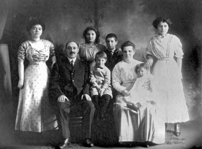 black and white posed photo of family of 8, mother and father both