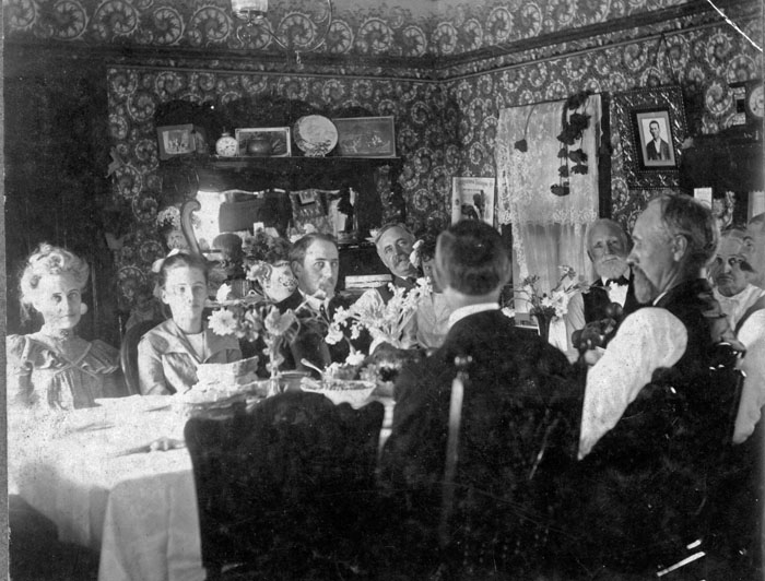 This family is all seated together for a family dinner. mealtimes were